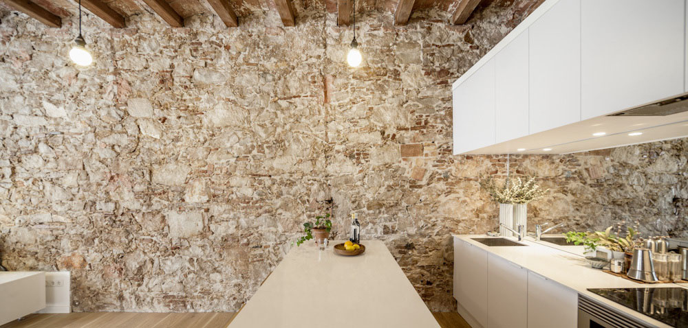 Minimalist White Kitchen with Rustic Stone Wall