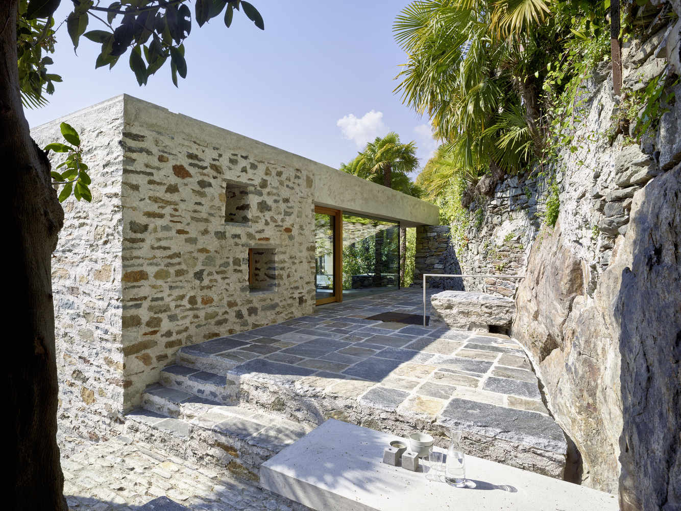Modern stone house with terraced garden overlooking lake for Modern stone houses architecture