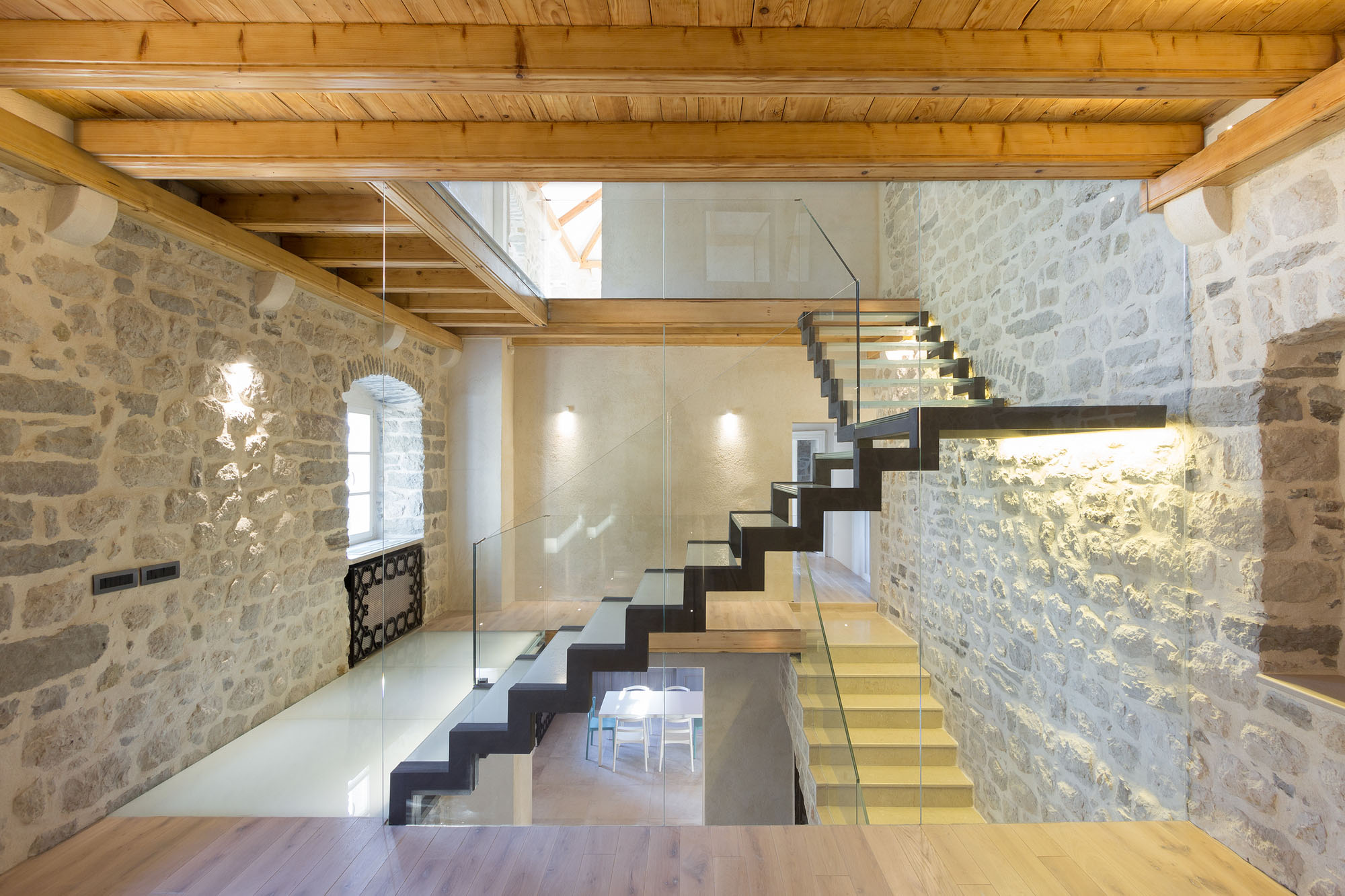 Rustic Stone Walls and Modern Glass Staircase