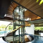 Tropical Home in Singapore with Spiral Staircase Wrapped Around a Glass Elevator