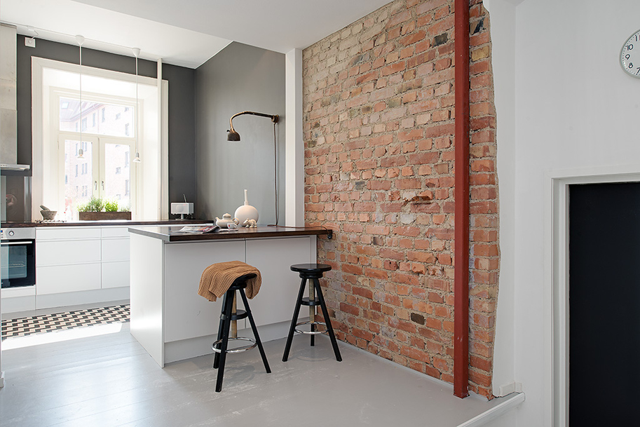 Modern White Kitchen with Rustic Brick Wall