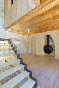 Living Room with Stone Walls, Fireplace, Natural Wood Floor and Glass Stairs